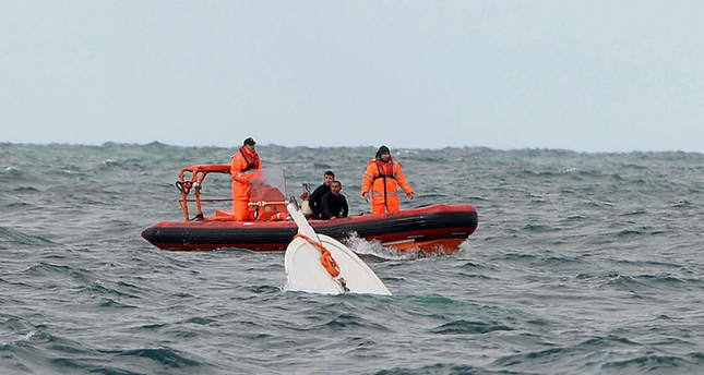 Two people detained over sinking immigrant boat