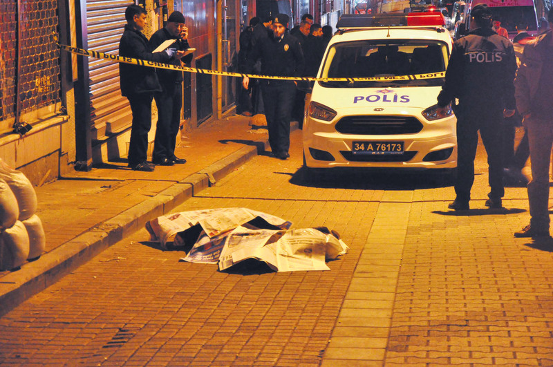 The body of Kuvatov lies on the ground covered in newspapers at the scene of the crime which was sealed off by police.