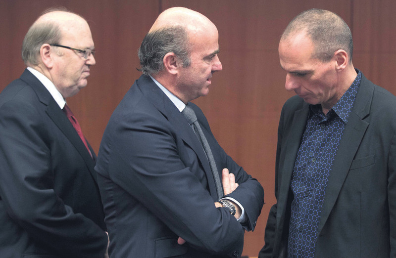 Irish Finance Minister Noonan (L) walks behind Spanish Economy Minister Guindos (C) and Greek Finance Minister Varoufakis at a eurozone finance ninisters meeting (Eurogroup) in Brussels yesterday.