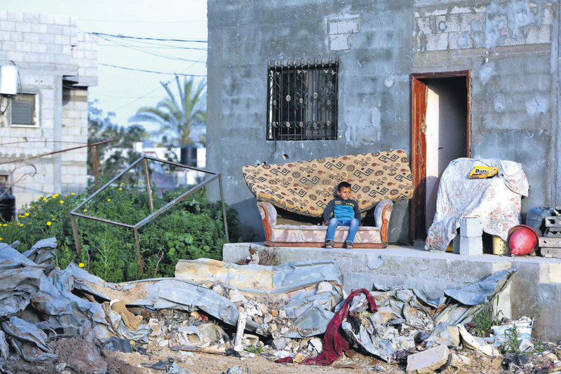 A Palestinian boy sits on a sofa outside his family's house that witnesses said was damaged by Israeli shelling during a 50-day war last summer in Khan Younis in the southern Gaza Strip.