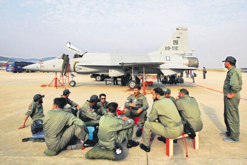 Pakistan air force personnel sit in front of their JF-17 jet fighter at the 8th China International Aviation and Aerospace Exhibition (Zhuhai Airshow) in Zhuhai, on the southern coast of Guangdong province China.