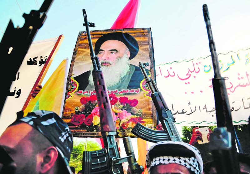 Shiite militias carry a poster of Shiite spiritual leader Grand Ayatollah Ali al-Sistani.