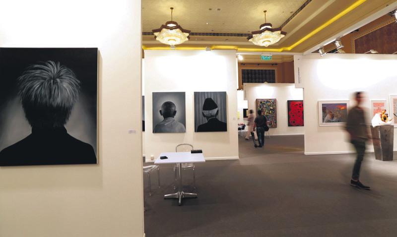 Visitors pass by art works titled ,Portraits, by Pakistani artist Ayaz Johio displayed at Art Dubai.