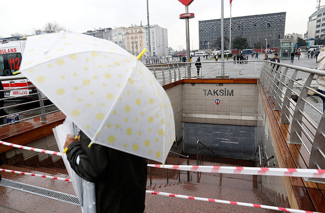 A street vendor sells umbrella in front of a closed subway station after a major power cut, at Taksim Square in Istanbul. (EPA Photo)