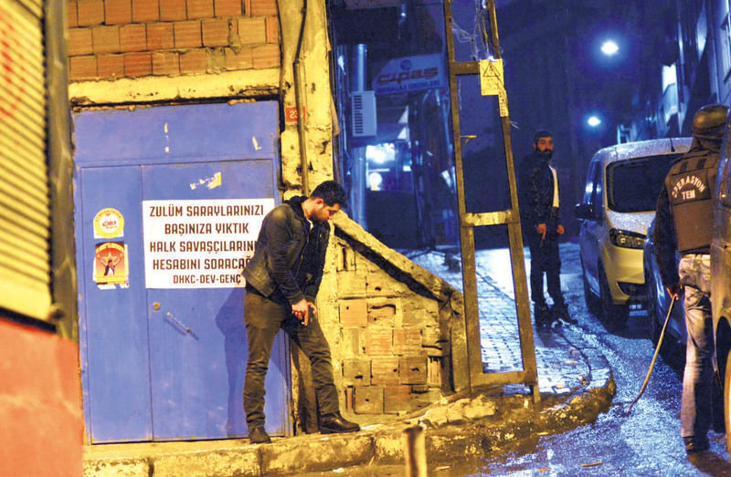 Plainclothes police officers stand outside a building in Okmeydanu0131 during an operation against the DHKP-C in the early hours of Thursday.