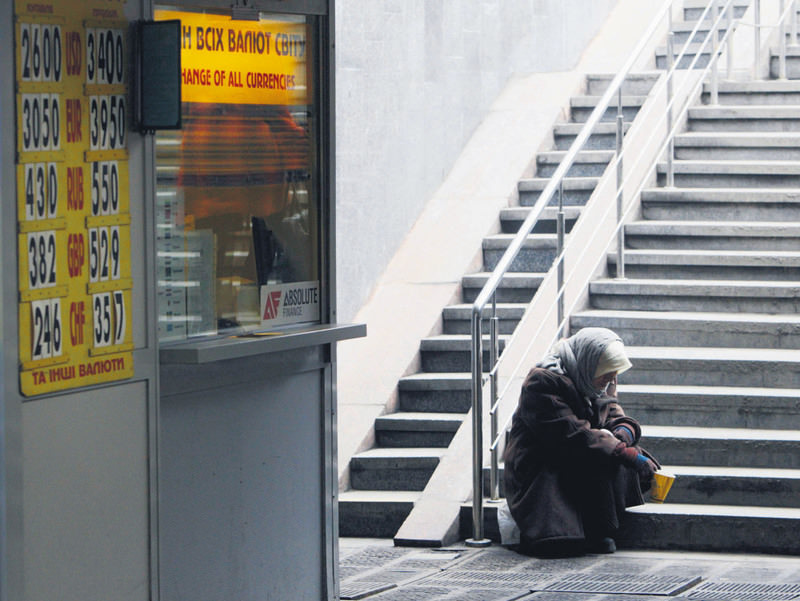 A woman sits next a currency exchange office in Kiev. A separatist war in the east of the country has made it difficult to stabilise an economy on the verge of bankruptcy.