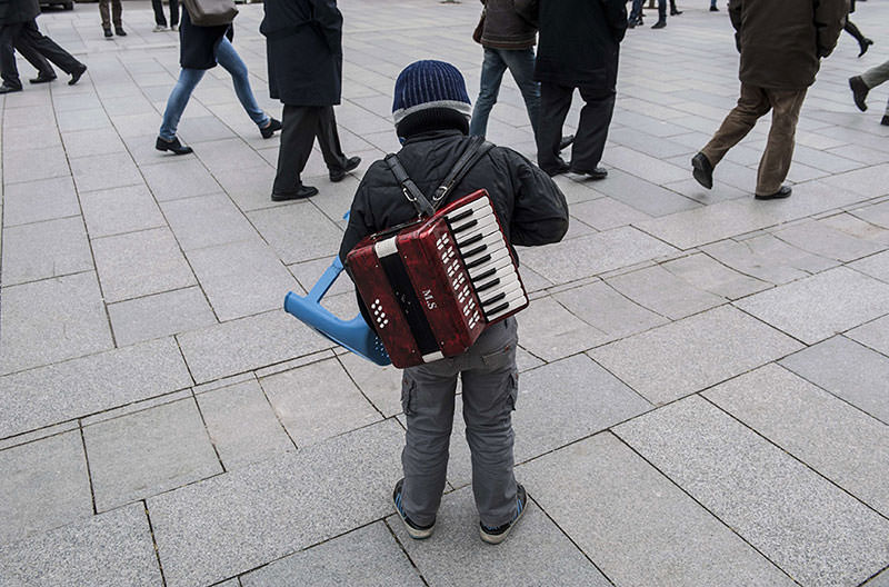 An ethnic Roma child counts his money after playing music for people on a small accordion  AFP Photo