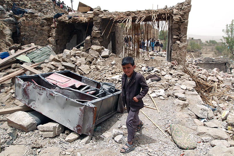A Yemeni boy walks past the rubble of destroyed houses in a village 70 kilometers west of Sanaa  AFP Photo