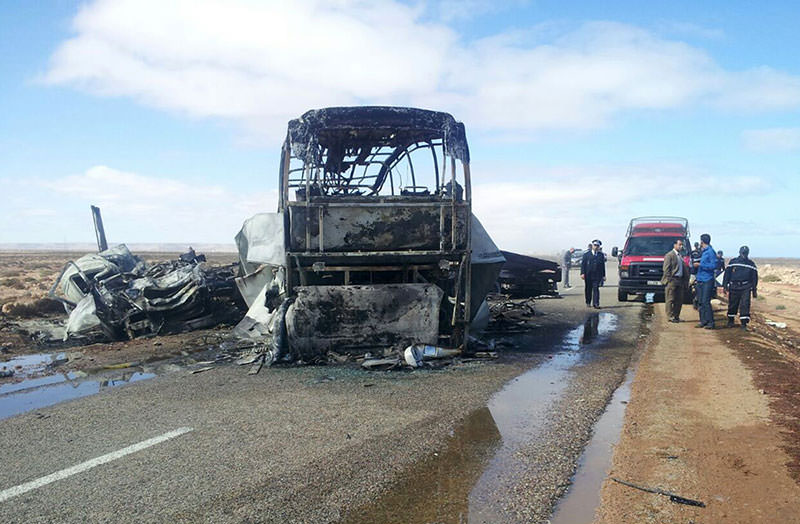 Emergency workers and officials inspect the burnt remains of the road accident (AP Photo)