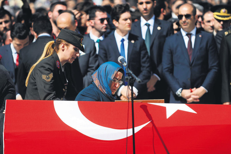 Yasemin Kiraz, wife of the late prosecutor, wailing beside the flag-draped coffin of her late husband at a funeral service in Istanbul.