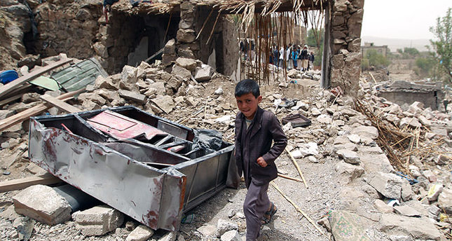 A Yemeni boy walks past the rubble of destroyed houses in a village 70 kilometers west of SanaaemAFP Photo/em