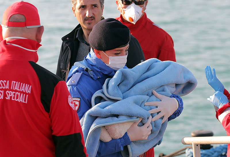 A Red Cross volunteer carries a baby wrapped in a blanket after migrants disembarked at the Sicilian Porto Empedocle harbor, Italy (AP Photo)