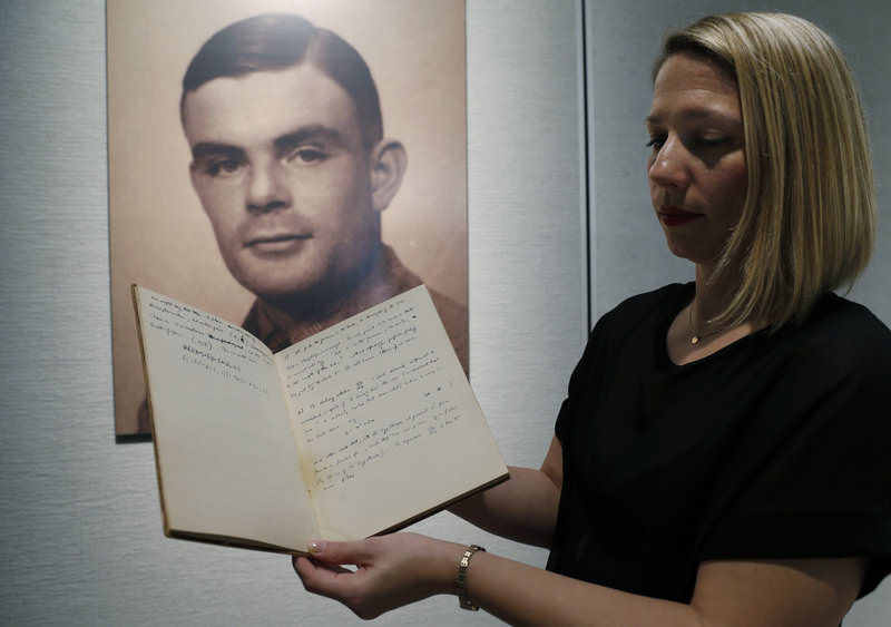 Cassandra Hatton, the director of the history of science at Bonhams auction house, shows the notebook of British mathematician and pioneer in computer science Alan Turing, in front of his portrait (Reuters Photo)