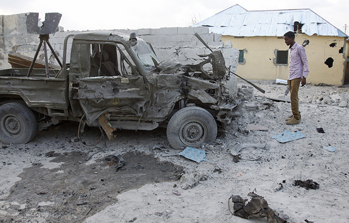 Somali man stands near the wreckage of a car that carried the bomb and was detonated at the gate of one of Mogadishu's most popular hotels on March 27  (AP Photo)