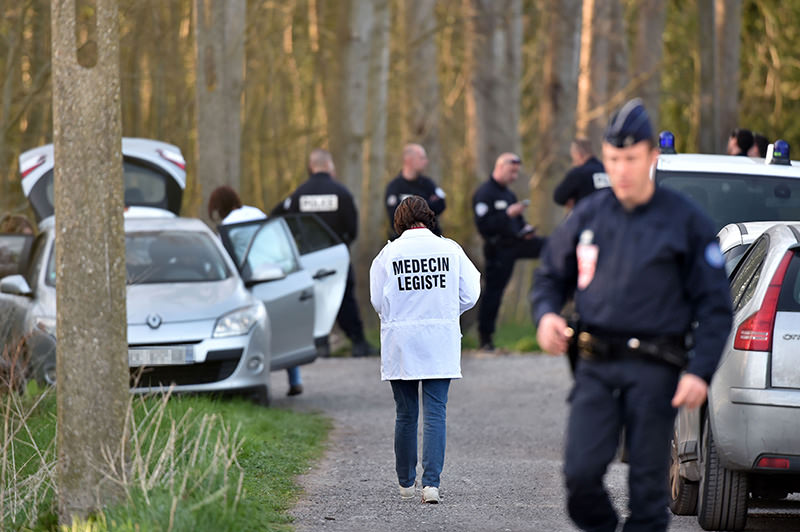 A medican examiner walks near the site in the Dubrulle forest where the dead body of an 8-year-old girl was found near the port of Calais, northern France, on April 15, 2015 (AFP Photo)