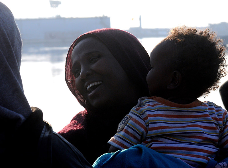 A migrant carries her baby as she smiles after disembarking from an Italian Coast Guard ship in the harbor of Palermo, Sicily, southern Italy, Tuesday, April 14, 2015 (AP Photo)