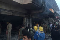 Emergency workers gather at the scene of a car bomb in northern city of Irbil, Iraq, Friday, April 17, 2015