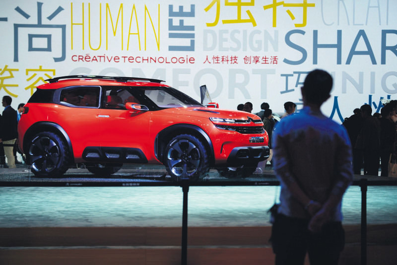 A man looks at a Citroen Aircross at the 16th Shanghai International Automobile Industry Exhibition in Shanghai. Chinese technology giants Alibaba and Tencent are promising to build the cars of the future.