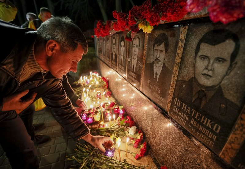 A man lights candles at a memorial, dedicated to firefighters and workers who died after the Chernobyl nuclear disaster, during a night service near the Chernobyl plant in the city of Slavutych, Ukraine (Reuters Photo)