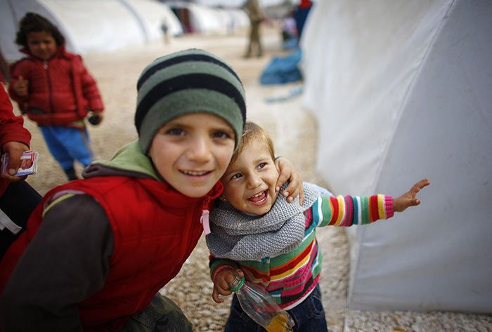 Refugee children, who are from the Syrian town of Kobani, smile as they play in a refugee camp in the border town of Suruu00e7, u015eanlu0131urfa province November 20, 2014 (Reuters Photo)