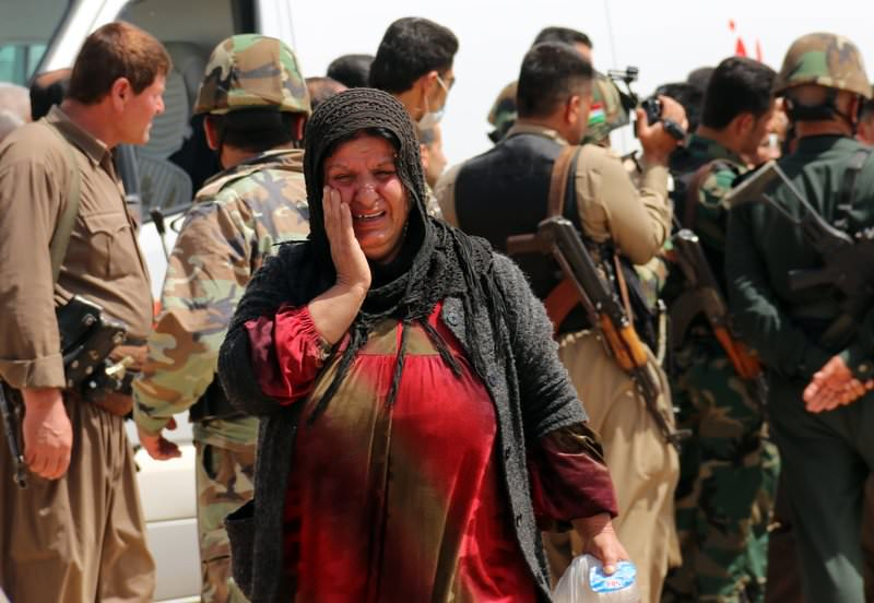 A Yazidi woman, released by ISIS, reacts upon her arrival in the village of al-Humeira, 35 kms southwest of Kirkuk, on April 8, 2015 (AFP Photo)