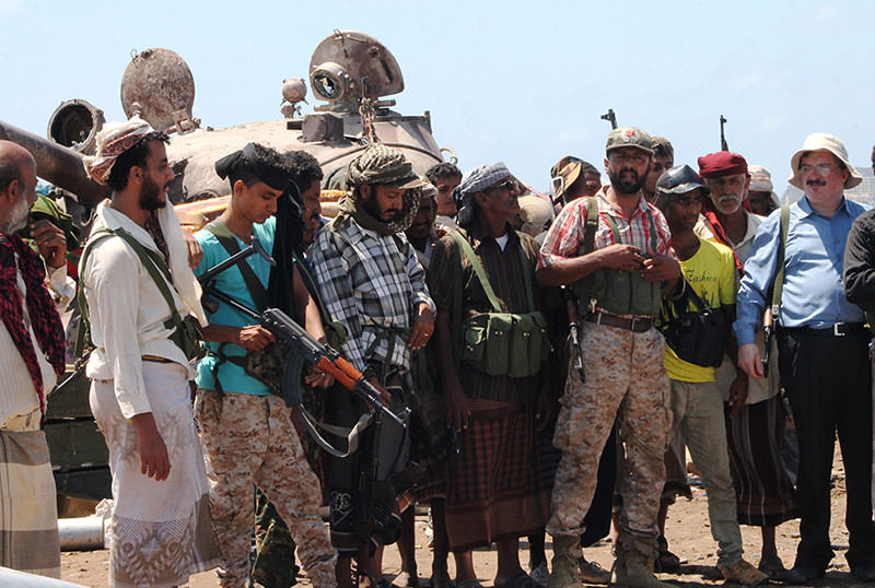 Armed tribal supporters of exiled Yemeni President Abedrabbo Mansour Hadi gather in front of a tank near the International airport in the port city of Aden (AFP Photo)