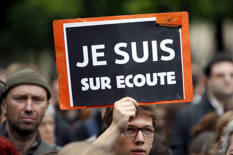 A protester holds up a placard which reads ,I know they tap my phones , as he demonstrates against the surveillance bill a day ahead of its vote in parliament in Paris May 4, 2015 (Reuters Photo)