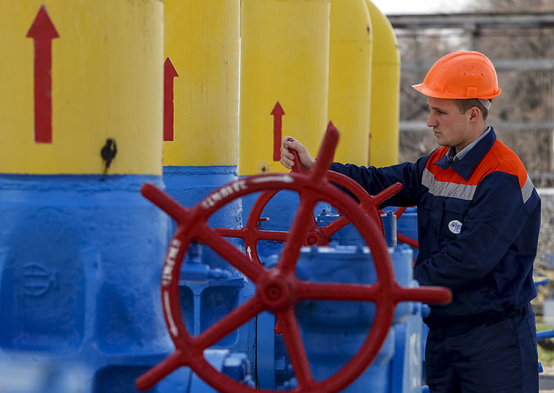 An employee turns a valve at a gas compressor station in the village of Boyarka, outside Kiev, April 22, 2015 (Reuters)