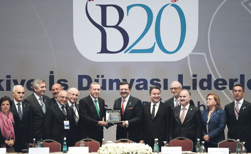 President Erdou011fan is presented a gift by B20 Chairman Hisarcikliou011flu during the Business World Leaders Forum in Istanbul on Friday.