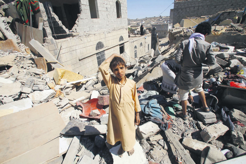 A boy stands in a rubble of houses destroyed by the Saudi-led airstrikes in Sanaa, Yemen, on Friday, May 1, 2015.