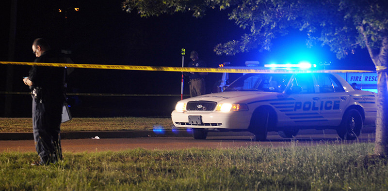 A Hattiesburg, Miss., lawman investigates the scene where two Hattiesburg police officers were shot to death, Saturday night, May 9, 2015 (AP Photo)