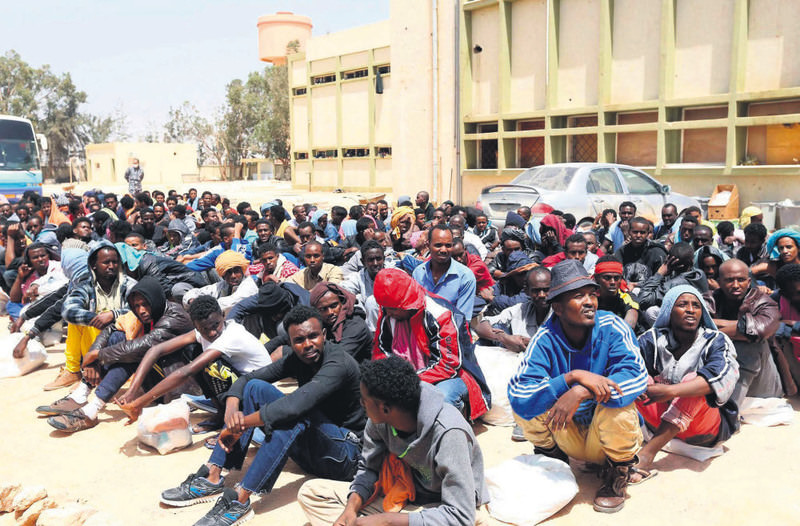 African Migrants sit in a center for illegal migrants in the al-Karem district in Misrata eastern of Tripoli, Libya on May 9, waiting to be transported to a different detention center.