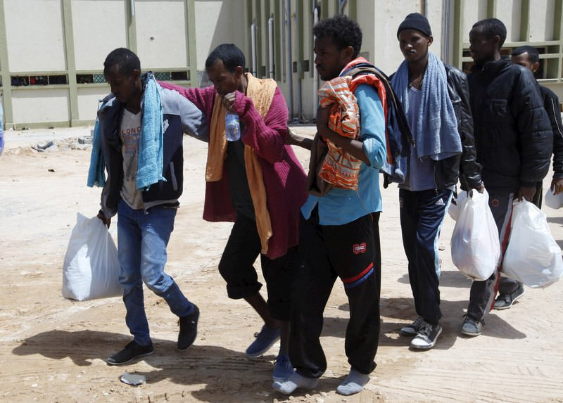 Migrants help another migrant walk to a bus bound for an immigration centre in the coastal city of Misrata, Libya, May 9, 2015 (Reuters Photo)