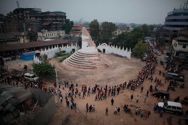In this Thursday, May 7, 2015, file photo, Nepalese people pay tribute to the victims of the April 25 earthquake, as they walk with lighted candles past the destroyed Dharahara tower in Kathmandu, Nepal (AP Photo)