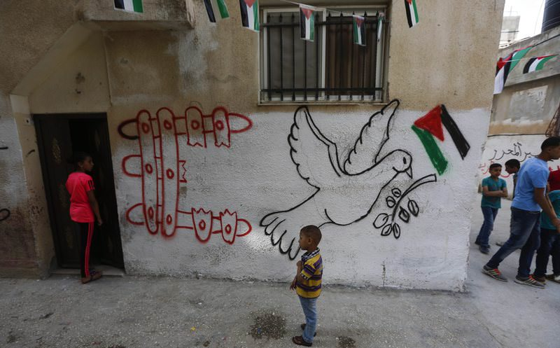 Palestinian children play close to a mural at the Al-Amarrie refugee camp near Ramallah (EPA Photo)
