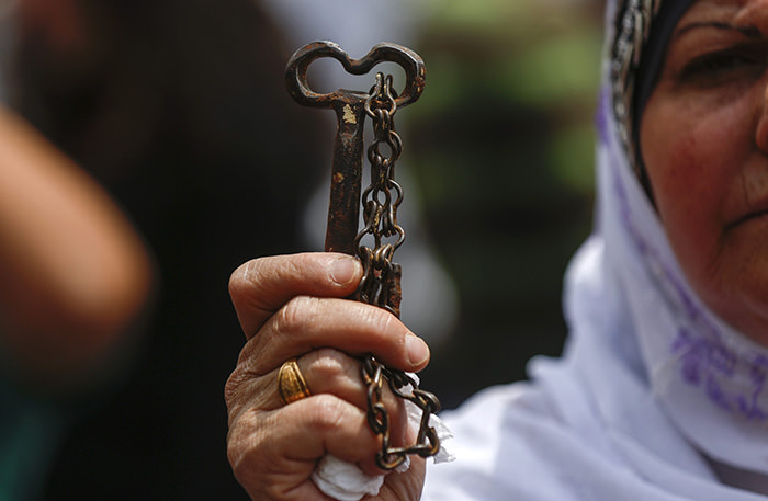 A Palestinian refugee holds up a symbolic key, allegedly from her old house, during a rally in the West Bank town of Ramallah, 13 May 2015, ahead of Nakba Day on 15 May  EPA Photo