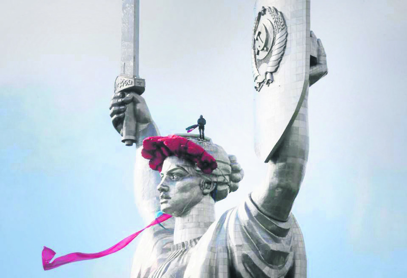 An anti-Russian protester in Kiev damages a statue that was erected by the Soviet Union.