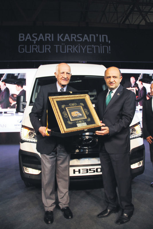 Ku0131rau00e7 (L), chairman of Karsan, presents a gift to Minister Iu015fu0131k (R) during the start of production ceremony for the Hyundai brand H350 series vehicles.