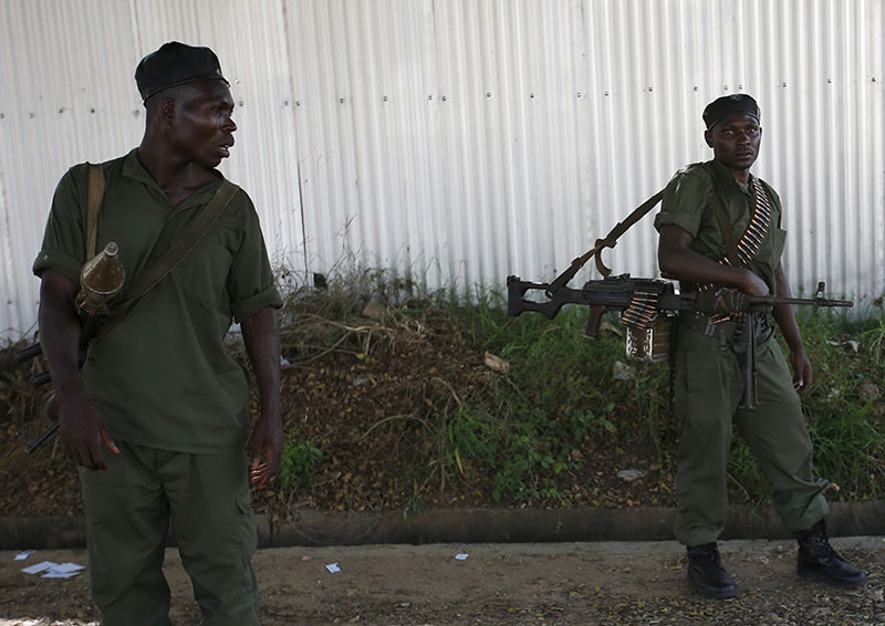 Soldiers, loyal to President Pierre Nkurunziza, hold weapons near the body of a soldier (not in picture), loyal to the coup leader, at a street in Bujumbura, Burundi, May 14, 2015 (Reuters Photo)