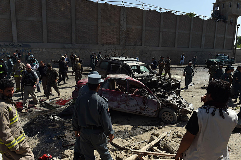 Afghan and foreign security forces inspect the site of a suicide attack in Kabul on May 17, 2015. (AFP Photo)