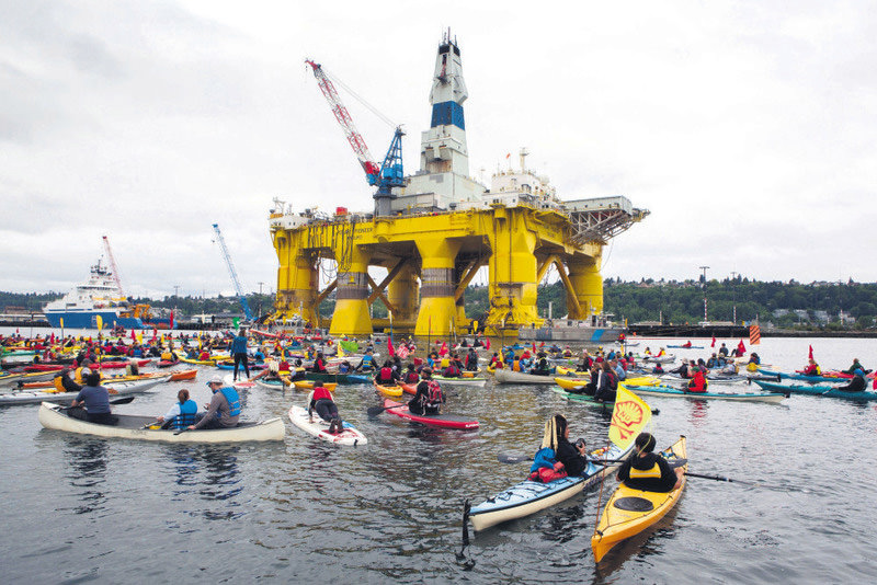 Activists in kayaks, who oppose Royal Dutch Shell's plans to drill for oil in the Arctic Ocean, approach Shell's Polar Pioneer drilling rig docked in Elliott Bay, next to the Port of Seattle's Terminal 5, during the ,Paddle in Seattle, protest