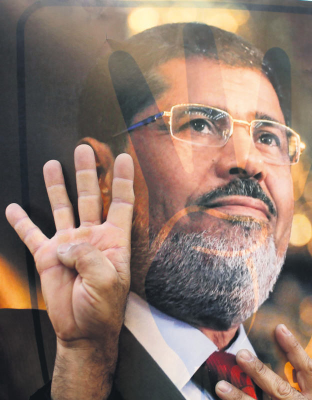 A protester in Cairo in front of a picture of Morsi makes the Rabaa sign (four) that became popular after hundreds of pro-Morsi protesters were massacred in Cairo's Rabaa Square.