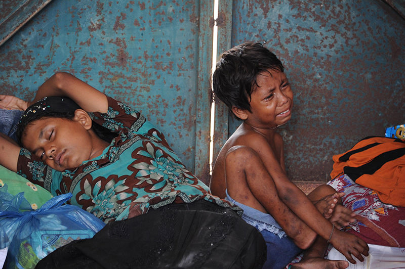 A young boy and his mother rest in a shelter after their arrival at the new confinement area in the fishing town of Kuala Langsa in Aceh province on May 15, 2015 (AFP Photo)