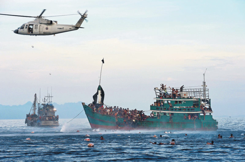 Rohingyan migrants try to collect the delivered food while any country does not accept them.