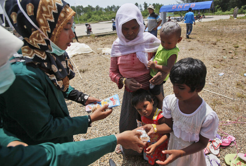 Acehnese students hand out snacks to ethnic Rohingya children at a temporary shelter in Langsa, Aceh province, Indonesia, Monday, May 18, 2015 (AP Photo)