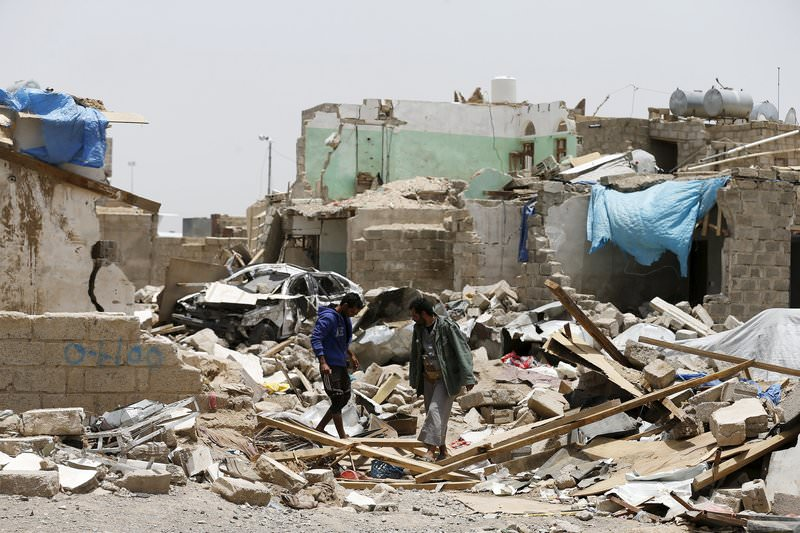 People walk at the site of a Saudi-led air strike that hit a residential area last month near Sanaa airport, May 18, 2015 (Reuters Photo)