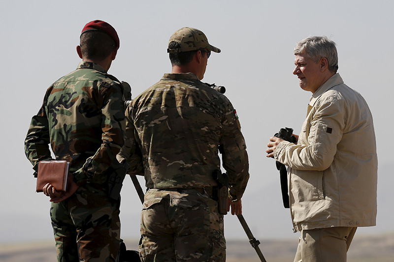 Canada's Prime Minister Stephen Harper (R) looks out towards Islamic State positions during his visit to Iraq in early May (Reuters Photo)