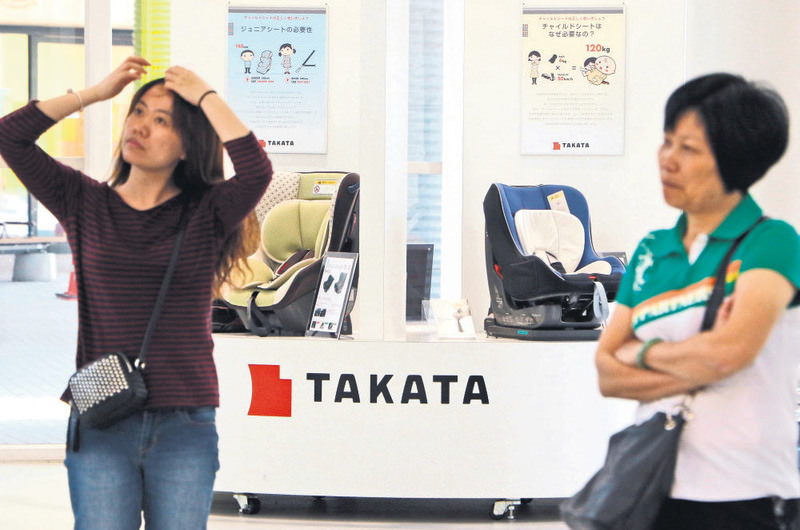 Japanese auto parts maker Takata's child car seats are displayed at a showroom in Tokyo yesterday. Takata is doubling a recall of US cars with potentially deadly airbags to a record nearly 34 million vehicles.