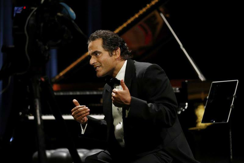 Syrian-American pianist and composer, Malek Jandali gestures on stage on May 16, 2015 in Dubai.