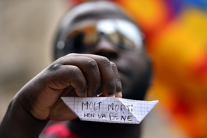 An asylum seekers holds a paper boat, with words written in Italian that read, ,Too many deaths, it is not good, during a demonstration in front of the Italian parliament in Rome, on April 23, 2015 (AFP Photo)